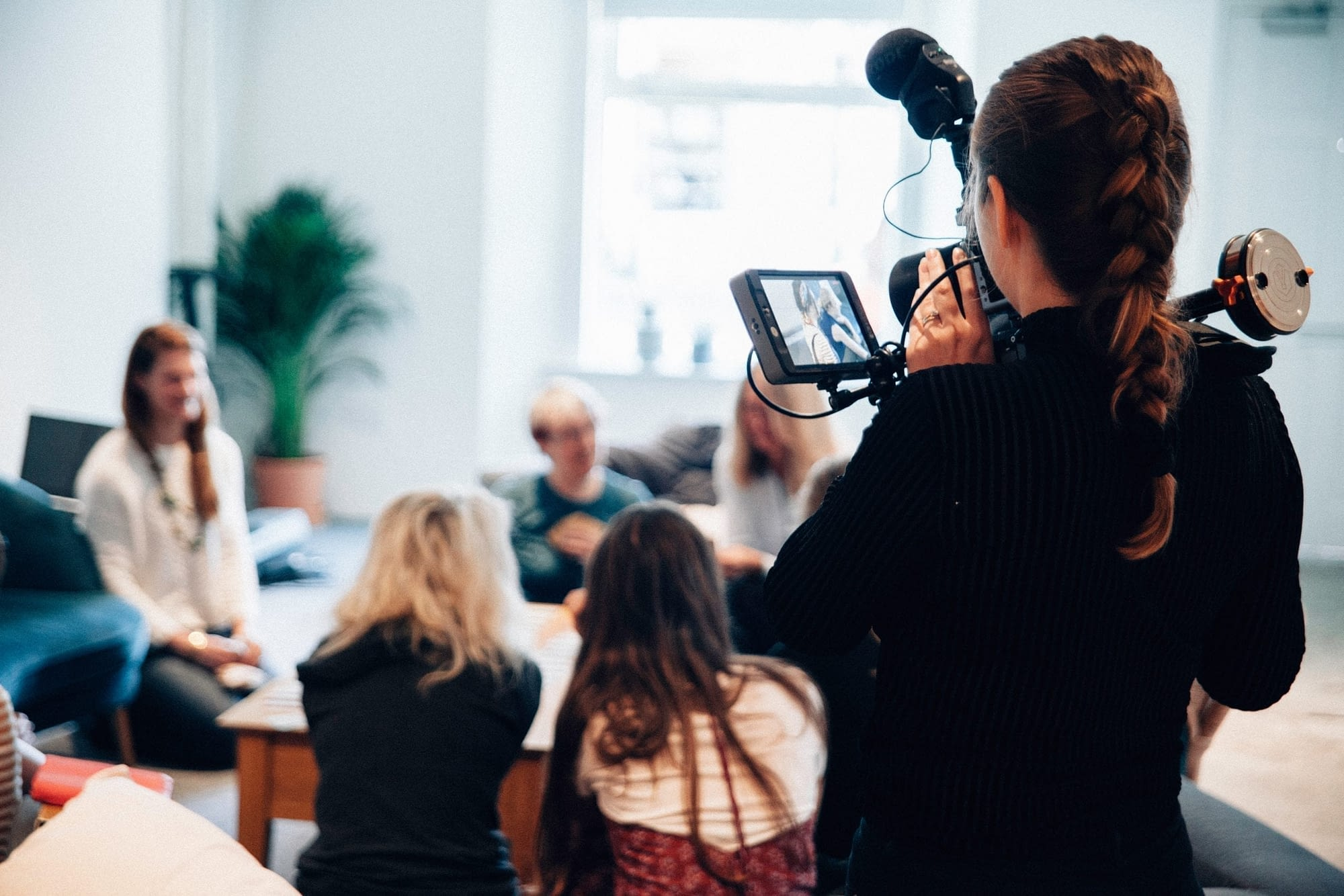 people in meeting with camera woman