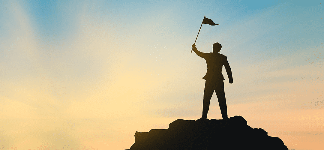 man standing on mountain with flag. Leader