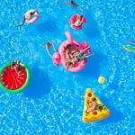 Friends having fun on colorful floaties at pool party